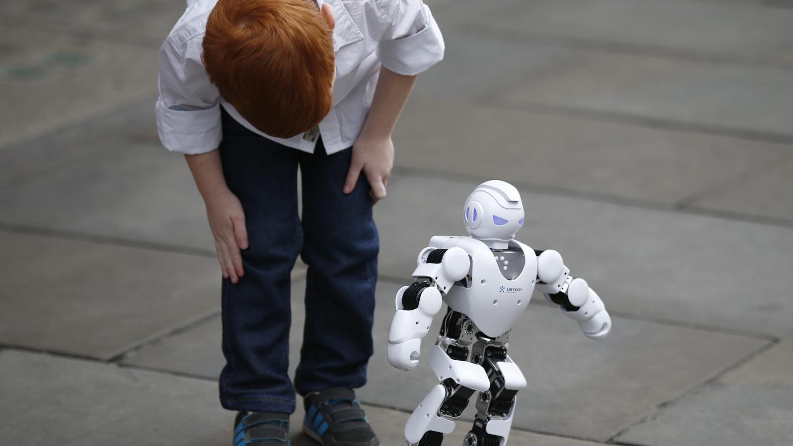a boy staring at robot
