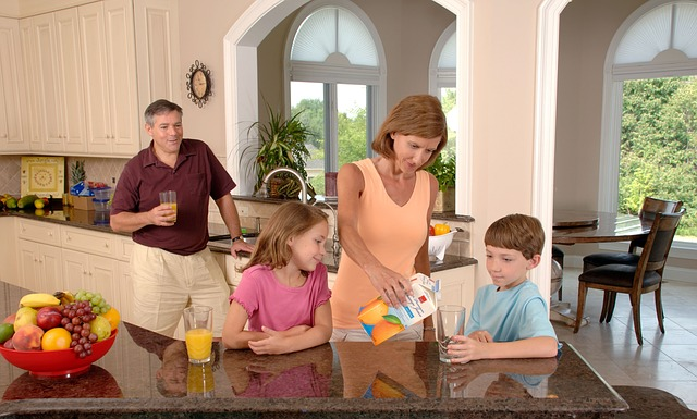 A family in the kitchen drinking juice.
