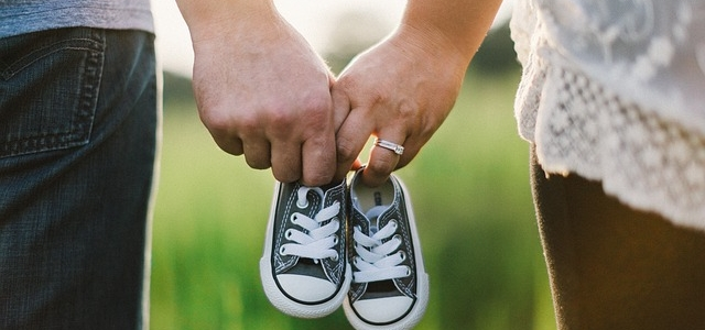 A couple holding baby shoes and preparing to start a family.